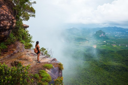 Woman standing on top of a mountain and looking out over the jungle