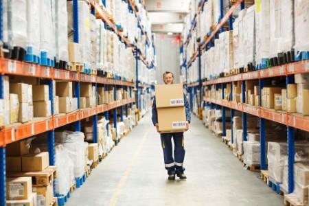 Working man carrying cardboard box  through aisle