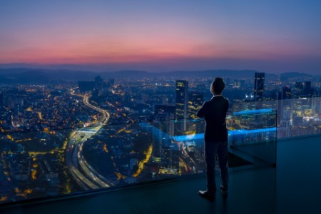 Businessman standing on open rooftop balcony watching city night view