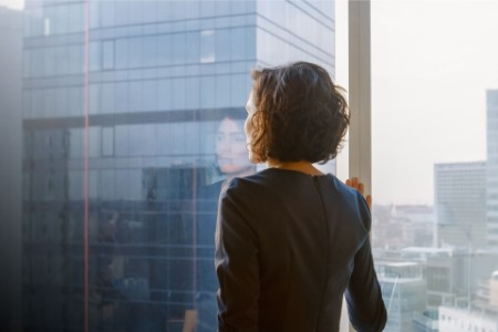 businesswoman looking out of her office window
