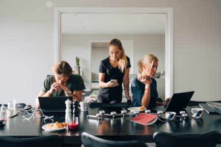 Family using technologies at dining table in room