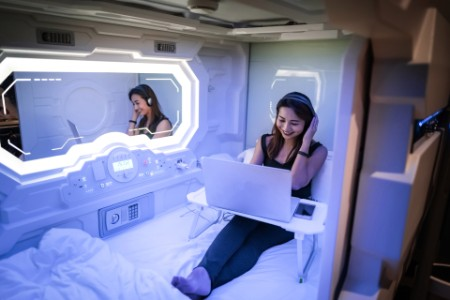 Woman listening to music in capsule hotel room