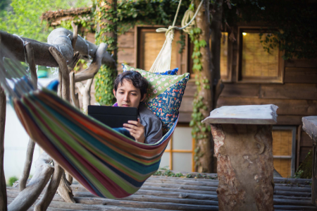 man with digital tablet laying in a hammock