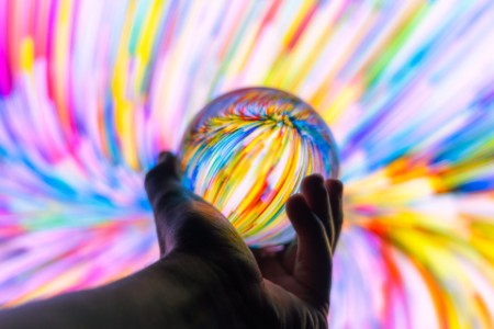 man holding a glass ball against colorful background