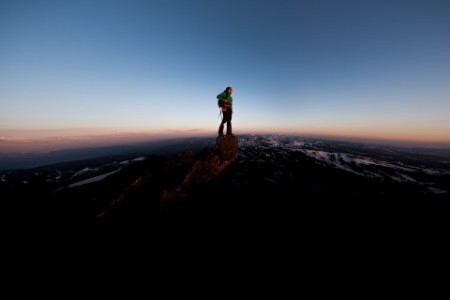 Mountain climber on the summit of a peak during sunset