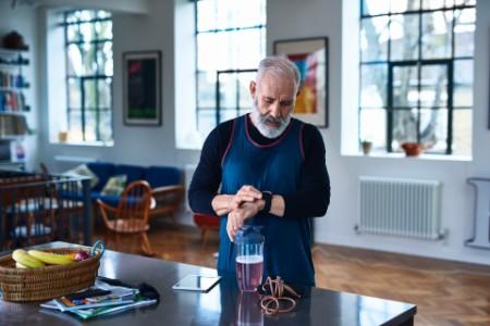 Senior man checking smart watch before exercising
