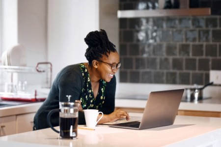 A women using her laptop on her kitchen counter and smiling