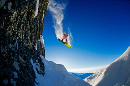 Snowboarder jumping over rocks Austria