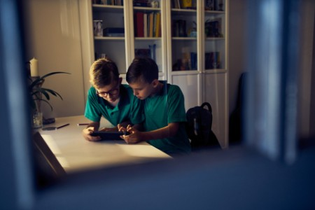 Two young boys using a digital tablet together