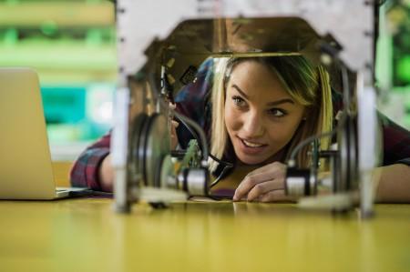 woman examining robot laboratory