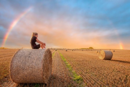Woman looking sat on hay Bales as a rainbow appears after a rain shower