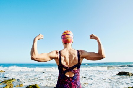 Woman swimmer flexing her muscles on beach