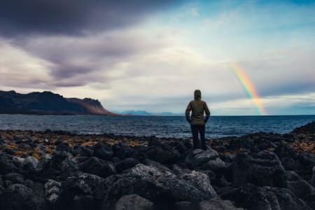 Woman watching rainbow over icelandic landscape
