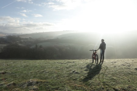 Woman with bike stood in field looking at view on frosty morning