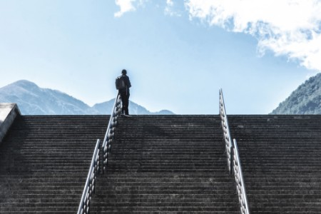 young man at the top of the stairs looking at the scenery