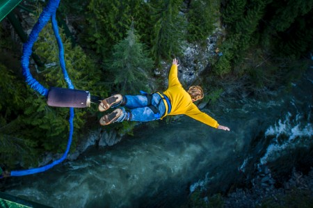 Young man bungee jumping over river
