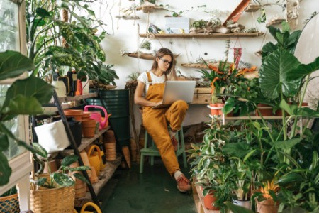 Young woman using laptop in a small garden room