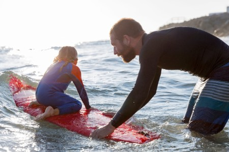 Father teaching daughter how to surf