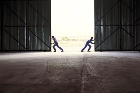 Mężczyźni otwierający drzwi do magazynu