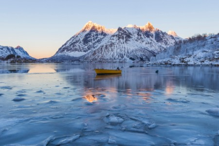 Winter scene of boat in partially frozen fjord and snowy mountain landscape