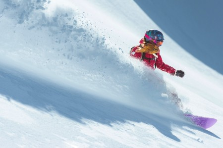 Woman snowboarding fresh snow