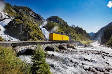 Yellow truck crossing bridge by waterfall in norway