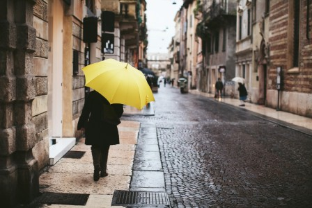 How strong mergers and acquisitions can reshape specialty finance - person walking down a street with a distinctively yellow umbrella