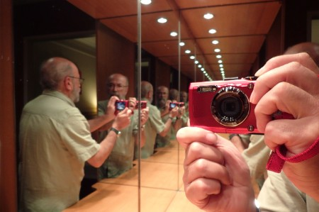 Mirror reflection of man taking photograph
