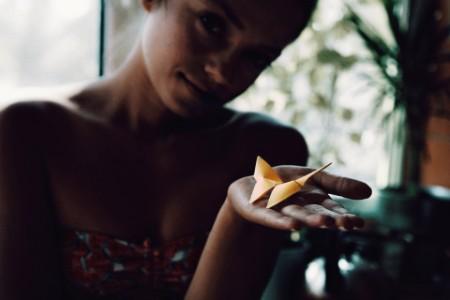 Primer plano de una mujer sosteniendo una mariposa de papel en su casa