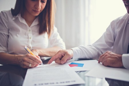 Woman is signing contract at her new work place