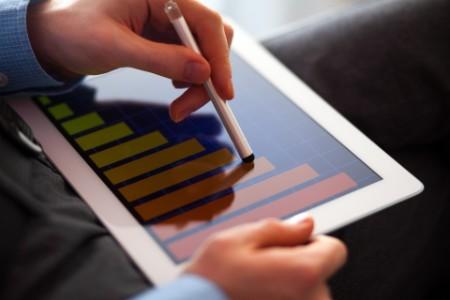 使用手寫筆與平板電腦上的條狀圖進行互動的商人