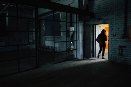 woman walking throught doorway in dark warehouse office