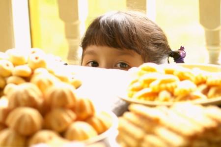 girl peeking table sweets