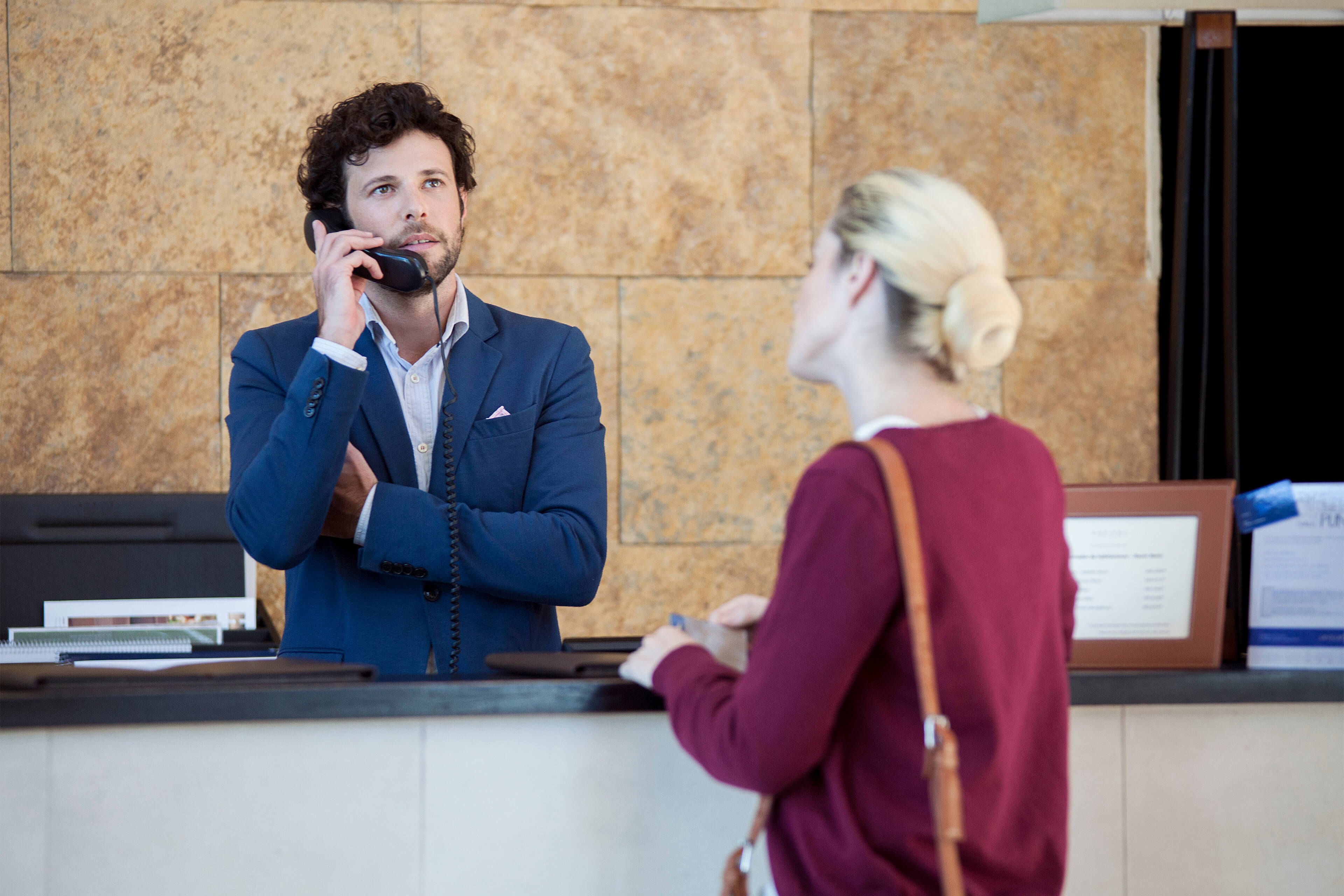 Male receptionist on the phone ignoring woman at the desk