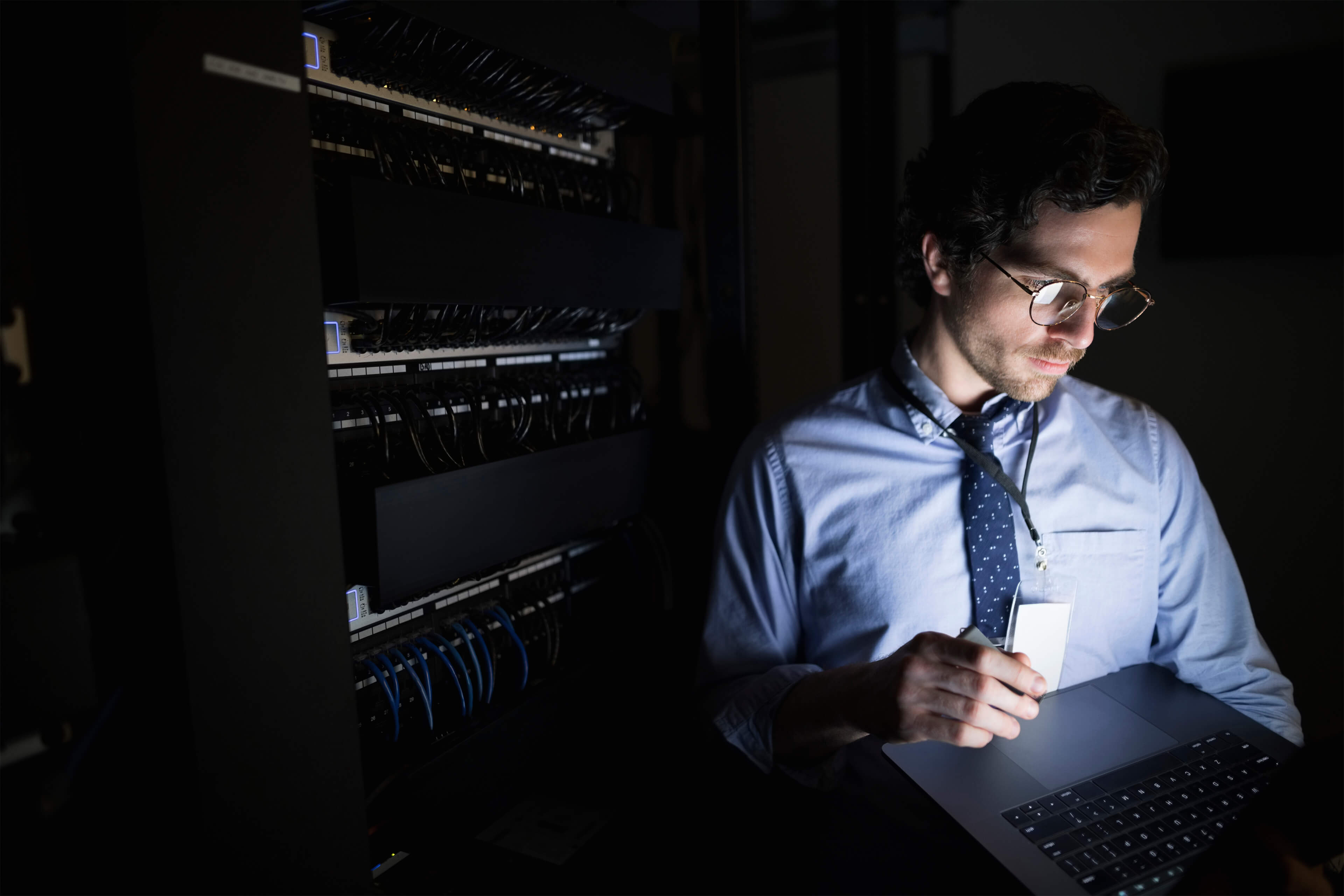 man checking tablet dark server room