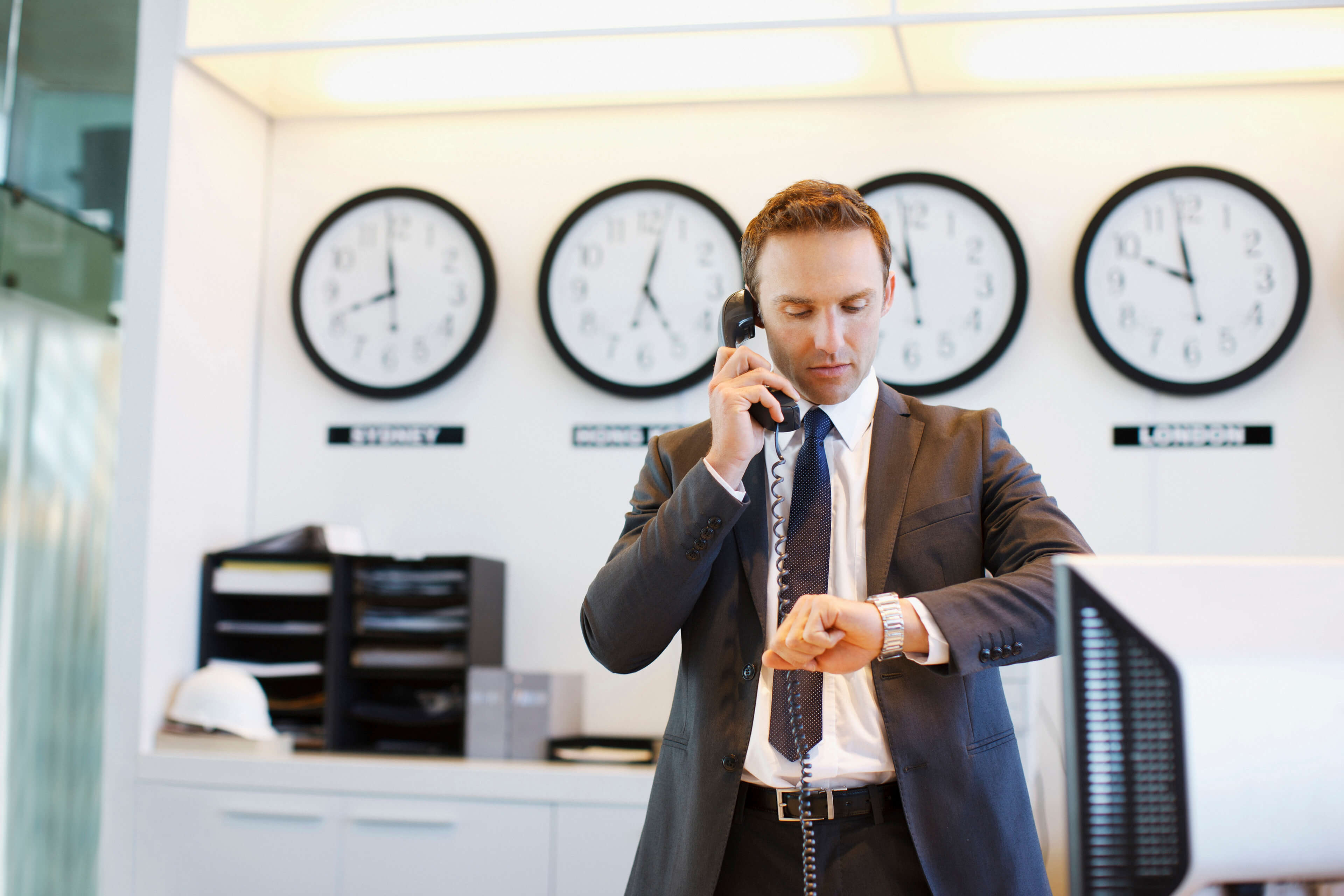 A man checks his watch in front of several clocks