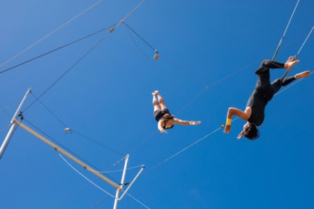 Trapeze artists practicing against the blue sky