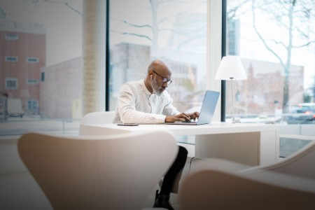 businessman with earphones sitting at desk working on laptop
