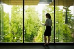 Businesswoman holding tablet standing at windows looking over green space