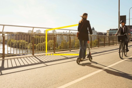 Commuters riding electric vehicles on bridge against blue sky