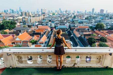 建物の上からバンコクの街中を見渡す女性