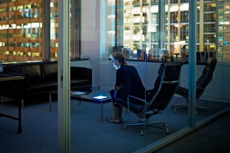 Woman with digital tablet in office at night