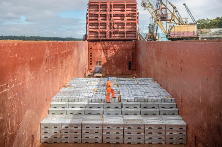worker standing metal ingots ship hold