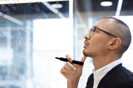 Business man looking plan glass wall office