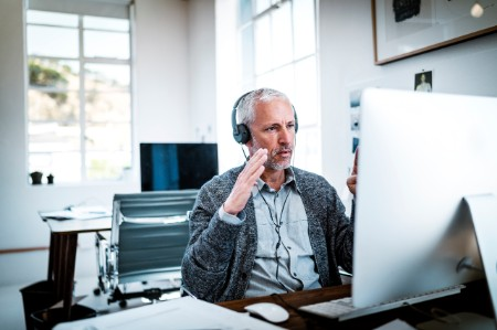 Man on headset at computer