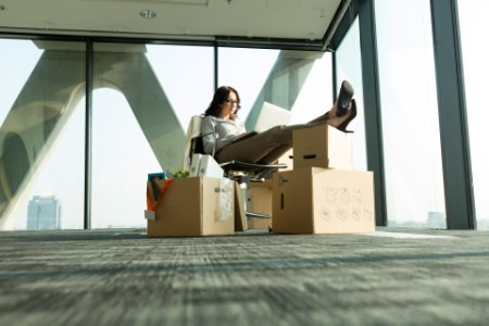 Businesswoman using laptop with feet on cardboard boxes