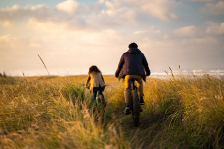 couple ride bicycles through grassy headlands above the ocean