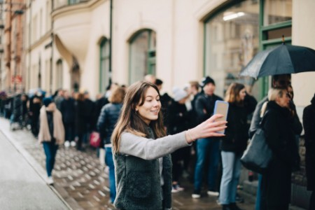 Girl taking selfie smart phone against crowd city