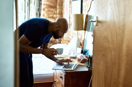 Man coffee checking emails laptop bedroom