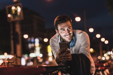 Young man at night with mobile phone